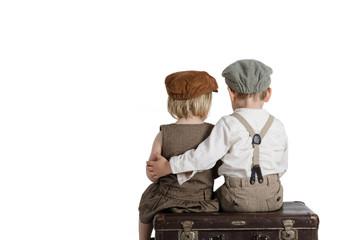 Zwei Kinder auf einem alten Koffer