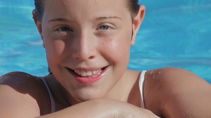 Blonde child girl in swimming pool (portrait - close up)