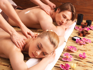 Attractive couple lying  in a spa salon.