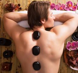 Man having stone massage in spa salon.