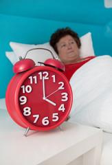 Ältere Frau liegt morgens um vier wach im Bett - Insomnie