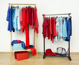 Tidy dressing closet with red and blue clothes hanging on a rack poster