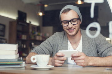 Hipster man with mobile phone at cafe