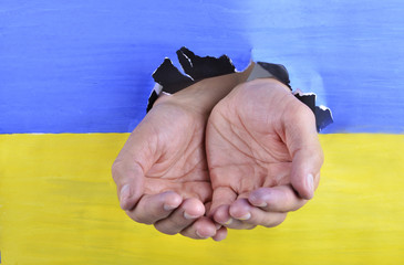 begging hands through Ukrainian flag