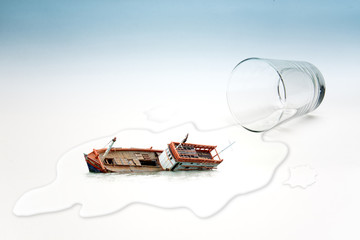 Empty glass of water with Boat capsized (surreal concept)