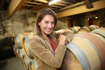 Smiling woman standing in wine cellar