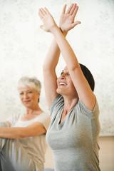 Frau in der Gymnastik Stretching Arme,ältere Frau im Hintergrund