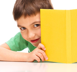 Little boy plays with book