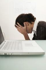 Junge Frau auf dem Schreibtisch,die Hände auf den Kopf,Seitenansicht sitzend