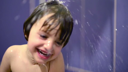 Happy kid in bathroom playing with water