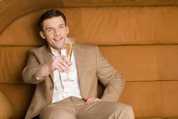 Man sitzt auf Sofa hält aus Champagner-Glas,lächelnd