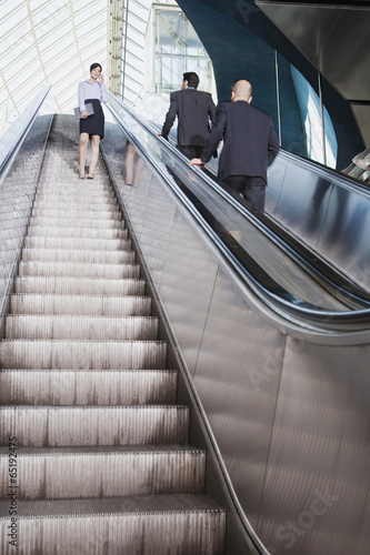 canvas print picture Deutschland,Bayern,München,Drei Geschäftsleute,die auf Rolltreppe,Geschäftsfrau mit Handy