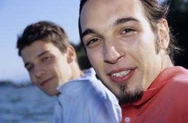 Zwei junge Männer sitzen auf Bootssteg,close-up,Portrait