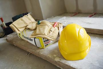 Bauarbeiterhelm und Werkzeuge auf Holzbrett