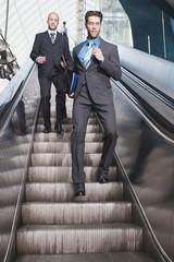Deutschland,Bayern,München,Drei Geschäftsleute,die auf Rolltreppe,Geschäftsmann läuft nach unten