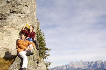 Junges Paar entspannt auf Berggipfel,Mann trinkt aus der Flasche