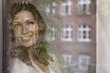 canvas print picture - Deutschland,Frau schaut aus dem Fenster und lächelnd