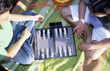 Zwei junge Männer spielen Backgammon,im Freien