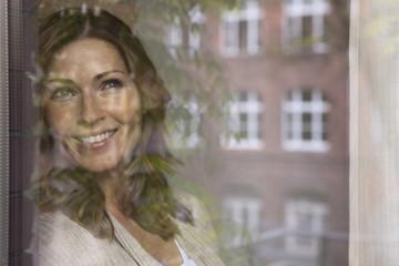 Deutschland,Frau schaut aus dem Fenster und lächelnd