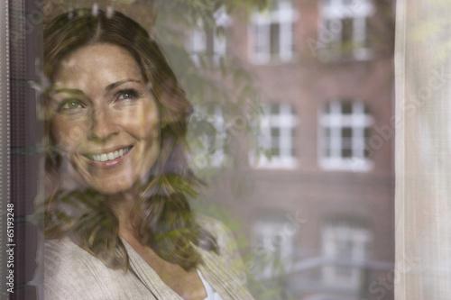 canvas print picture Deutschland,Frau schaut aus dem Fenster und lächelnd