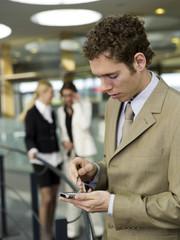 Junger Geschäftsmann mit Handy,Frauen reden im Hintergrund