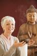 Portrait einer älteren Frau,Buddha-Statue im Hintergrund