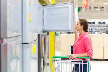 A woman buys a refrigerator in the store