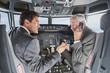 Deutschland,Bayern,München,Geschäftsleute sprechen auf Handy im Flugzeug-Cockpit