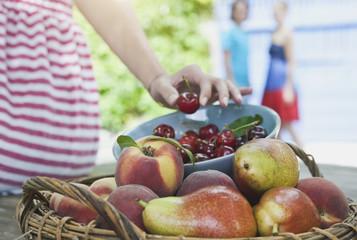 Italien,Toskana,Magliano,Frau,die Kirsche in der Nähe von Obstkorb auf Holztisch