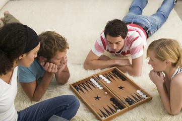 Vier junge Menschen auf dem Boden,spielen Backgammon
