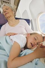 Deutschland,München,Bayern,Senior Frau und Mädchen,die schlafen neben Fenster in der Economy- Klasse-Verkehrsflugzeug