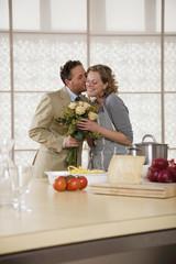 Junges Paar in der Küche mit Blumen-Bouquet