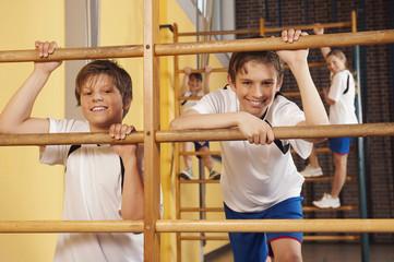 Deutschland,Emmering,Jungen (12-14) Kletterwand Bars mit Mädchen im Hintergrund