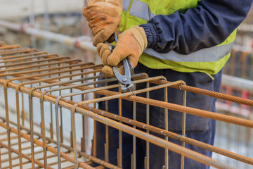 workers hands using steel wire and pincers to secure rebar