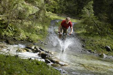 Mountainbiker überquert einen Bach