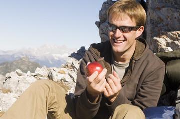 Österreich, Salzburger Land , Junger Mann hält einen Apfel