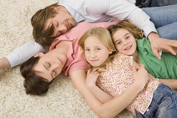 Familie auf dem Boden liegend im Wohnzimmer,erhöhte Ansicht