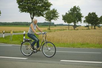 Ältere Frau Radfahren auf der Straße