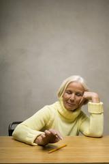 Ältere Frau,die am Tisch sitzen,Blick nach unten