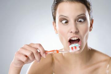 Junge Frau putzt sich die Zähne , lächelnd , close up