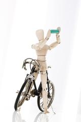 Holzfigur als Radfahrer haltet eine Pille in Hände