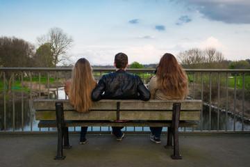 drei personen auf einer parkbank