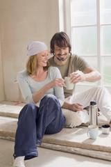 Junge Paare,die auf der Baustelle eine Pause