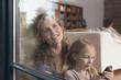 canvas print picture - Deutschland,Köln,Mutter und Tochter ( 6-7 ) sitzen am Fenster,der Vater im Hintergrund,Portrait