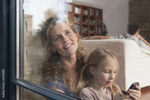 canvas print picture Deutschland,Köln,Mutter und Tochter ( 6-7 ) sitzen am Fenster,der Vater im Hintergrund,Portrait