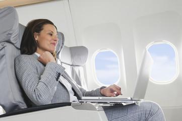 Deutschland,Bayern,München,Geschäftsfrau mit Laptop in der Business Class Flugzeugkabine