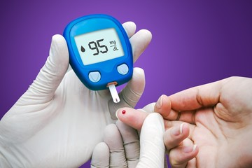 Doctor making blood sugar test. Hands with gloves on medical bac