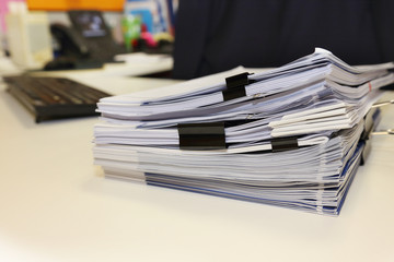 pile of documents on the office desk