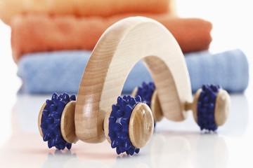 Massage -Tool mit Handtüchern im Hintergrund