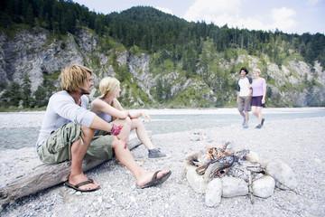 Deutschland,Bayern,Tölzer Land,Junge Leute sitzen am Lagerfeuer in der Nähe Fluss